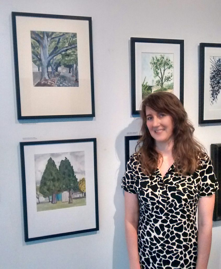 photo of artist Alexandra Schaefers with two of her treescapes at the Elizabeth Jones Art Center in Portland, Oregon